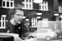 Man i trådlös hörlurar på resaurant, gata, restaurang Mannen som lyssnar till eBook, grabben, lyssnar till musik arkivfoton