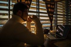 Man i tröjan som arbetar på bärbara datorn i caffe på solnedgång arkivbilder