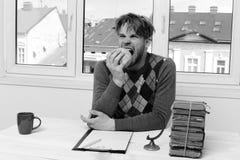 Man i tröjasammanträde på skrivbordet med bunten av böcker arkivfoton