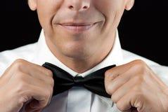 Man i Tux Straightens Bowtie, två händer royaltyfria bilder