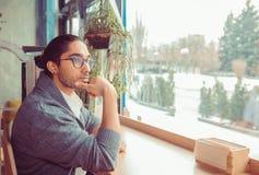 Man i vardagsrum som ser till och med fönster och att vara fundersamt fotografering för bildbyråer