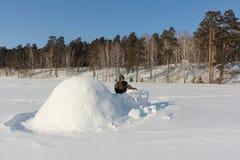 Man i varm kläder som bygger en igloo på en snöig glänta i vintern, Sibirien, Ryssland royaltyfri foto