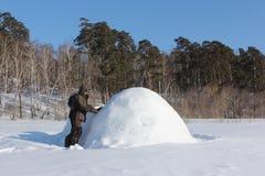 Man i varm kläder som bygger en igloo på en snöig glänta i vintern, Sibirien, Ryssland arkivfoto