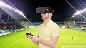 Man i virtuell verklighethörlurar med mikrofon över fotbollfält Arkivfoto