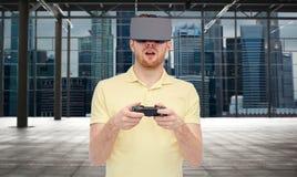 Man i virtuell verklighethörlurar med mikrofon med gamepad Arkivfoton