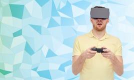 Man i virtuell verklighethörlurar med mikrofon med gamepad Fotografering för Bildbyråer
