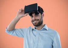 Man i virtuell verklighethörlurar med mikrofon mot persikabakgrund Fotografering för Bildbyråer
