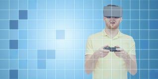 Man i virtuell verklighethörlurar med mikrofon med gamepad Royaltyfria Bilder
