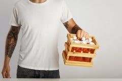 Man i vit t-skjorta utan etikett med asken av orange drinkar royaltyfria bilder