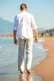Man i vita kläder som promenerar stranden Arkivbild