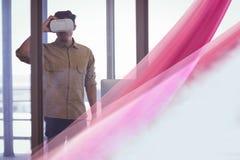 Man i VR-hörlurar med mikrofon som ser den rosa ljusa manöverenheten royaltyfri bild
