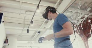 Man i VR-hörlurar med mikrofon som spelar leken stock video
