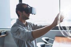 Man i VR-hörlurar med mikrofon som trycker på en manöverenhet för sfär 3D Royaltyfri Bild