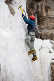 Man with ice axes and crampons. Climbing on icefall stock photo