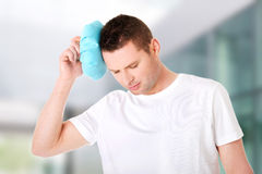 Man with ice bag for headaches Stock Image