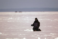Man Ice Fishing. A man sits patiently while ice fishing on a cold winter day Royalty Free Stock Images