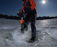 Man ice fishing and drilling hole in the ice Royalty Free Stock Image