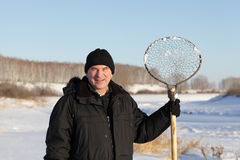 Man with ice fishing skimmer Stock Images