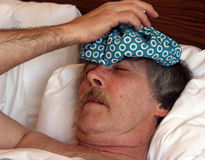 Man with ice pack on head. Sick mature man in bed with ice bag or pack on forehead royalty free stock photos