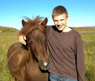 Teenager with Icelandic horse. Handsome young man with arm around Icelandic horse, green fields in background royalty free stock photos