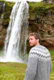 Man in Icelandic sweater by waterfall on Iceland Royalty Free Stock Photography