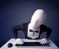 Man without identity working with keyboard on blue background Stock Images