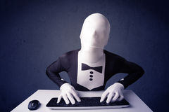 Man without identity working with keyboard on blue background Royalty Free Stock Image