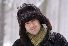Man if furry hat. Smiling man in fur hat in the snow stock images