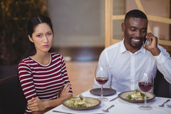 Man ignoring bored woman while talking on mobile phone. In restaurant Stock Photo