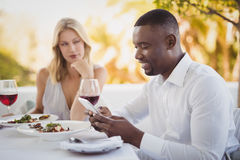 Man ignoring bored woman while using mobile phone Stock Image