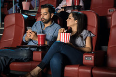 Man ignoring his date and the movie. Distracted men using his phone while ignoring his date and a movie at the cinema theater Royalty Free Stock Images