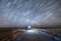 Man illuminating a beach path under star trails. Star trails over strathmere beach in New Jersey Stock Images