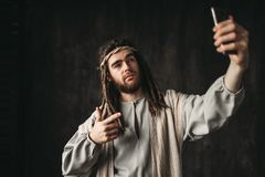 Man in the image of Jesus Christ makes selfie. On phone, dark background. Gadgets from the evil one Royalty Free Stock Photos