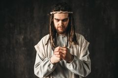 Man in the image of Jesus Christ praying. Dark background. Belief in god, christian faith Stock Photos