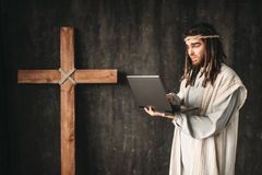 Man in the image of Jesus Christ uses laptop. Crucifixion cross on black background. Believers and modern technologies concept Royalty Free Stock Photography