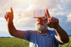 Man imagining in 3D glasses. Imagining virtual reality on field of weed, man Looking directly, both hands up, fingers pointing, close-up shot Stock Images