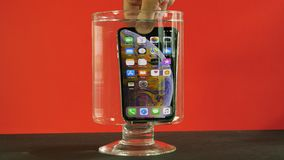 Man immersing new Apple Computers iPhone Xs Max in water. PARIS, FRANCE - CIRCA 2018: Man immersing new Apple Computers iPhone Xs Max smart phone with all home stock video footage