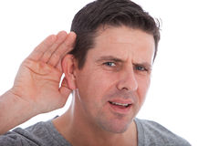 Man with impaired hearing struggling to hear. Frowning as he holds his hand to his ear in an attempt to improve acoustics Stock Images