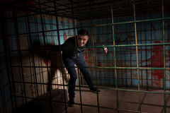 Man imprisoned in a metal cage with a blood splattered wall behi Royalty Free Stock Photography
