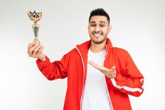 Man In A Red Tracksuit Shows Off The Winner`s Gold Cup On A White Background Stock Photos
