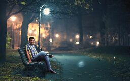 Free Man In Blue Denim Jeans Sitting Down By Wooden Bench Near Post Lamp Lighted Stock Photo - 82931310