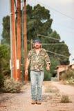 Man In Camoflauge Walking On Dirt Road Royalty Free Stock Photos