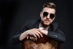 Free Man In Glasses Sits On A Chair. Businessman Confident Man. SEO Manager Posing On A Black Background. Successful Entrepreneur. Stock Photo - 99453460