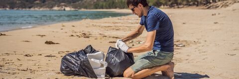 Free Man In Gloves Pick Up Plastic Bags That Pollute Sea. Problem Of Spilled Rubbish Trash Garbage On The Beach Sand Caused Royalty Free Stock Photography - 193828337