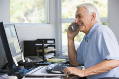 Man In Home Office On Telephone Using Computer Royalty Free Stock Images