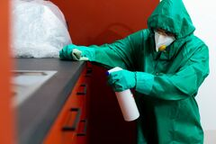 Free Man In Protective Suit Spraying Chemicals On Kitchen Cabinetry Royalty Free Stock Photography - 180987797