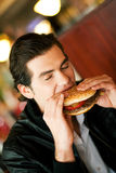 Man In Restaurant Eating Hamburger Royalty Free Stock Images