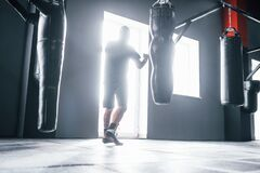 Free Man In Sportive Clothes Training Boxing In The Gym With Pushing Bags. Illuminated By Light Royalty Free Stock Photography - 199667477
