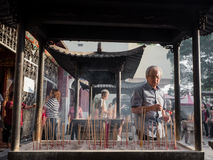 Man with Incense Praying at Chinese Temple. A man prays at a Chinese Temple as he leaves incense. Morning light strikes his profile Stock Photo