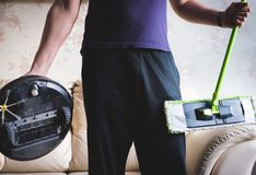 Man includes a robotic vacuum cleaner and holds. Mop Stock Image